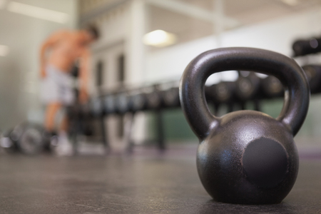 gym room: Focus on large black kettlebell in weights room at the gym Stock Photo