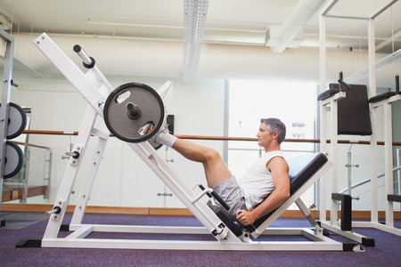 active lifestyle: Fit man lifting heavy barbell with legs at the gym