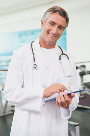 doctor computer: Confident doctor standing in fitness studio using tablet pc at the gym