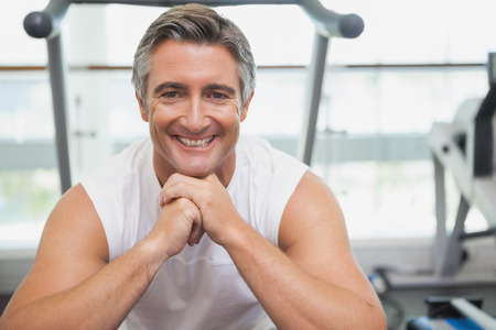 Fit man smiling at camera in fitness studio at the gym Stock Photo