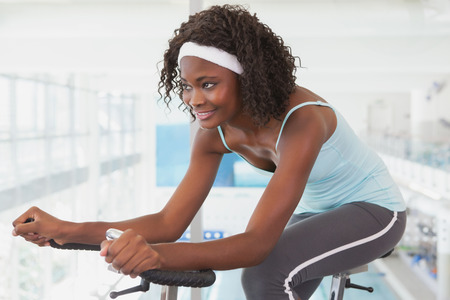people exercising: Fit woman working out on the exercise bike at the gym Stock Photo