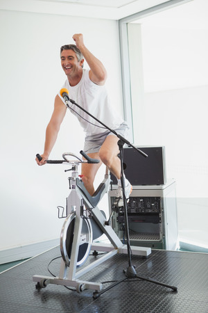 motivating: Spinning instructor motivating his class at the gym