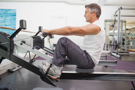 man working out: Fit man working out on rowing machine at the gym