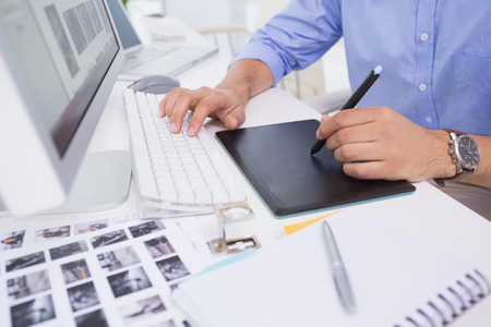 graphics: Graphic designer using digitizer at his desk in creative office Stock Photo