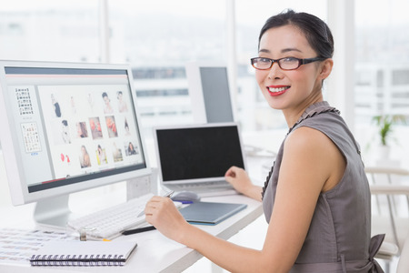 designed: Photo editor working at her desk in creative office Stock Photo