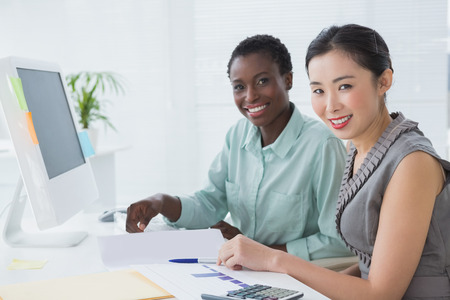 Businesswomen working together at desk in creative office photo