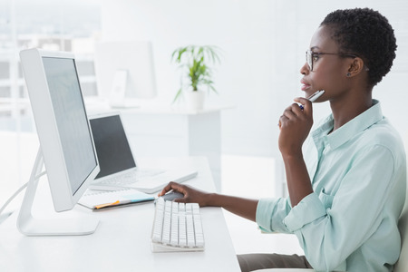 Focused businesswoman working at desk in creative office