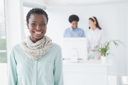 business: Casual businesswoman smiling at camera in creative office