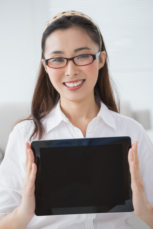 Businesswoman sitting and showing tablet in creative office photo