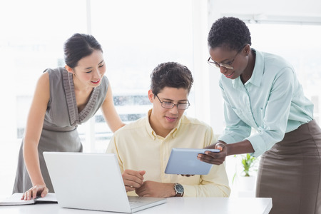 Casual business team looking at tablet together in creative office photo