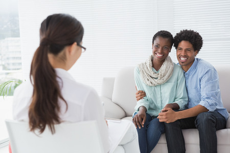 Reconciled couple smiling at their therapist in therapists office