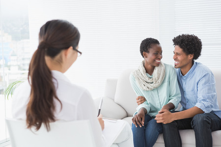 counselling: Reconciled couple smiling at each other in therapists office