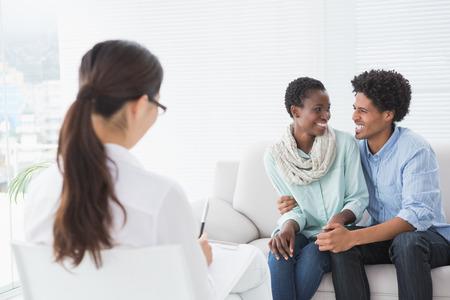 Verzoend paar glimlachen bij elkaar in therapeuten kantoor