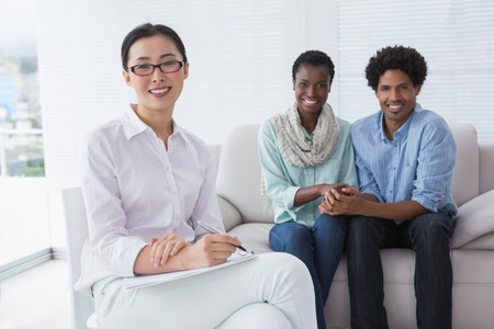 psychiatry: Reconciled couple smiling at camera with therapist in therapists office