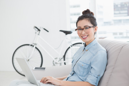 Young creative woman using laptop on couch in creative office photo