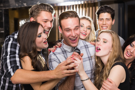 karaoke bar: Happy friends singing karaoke together in a bar