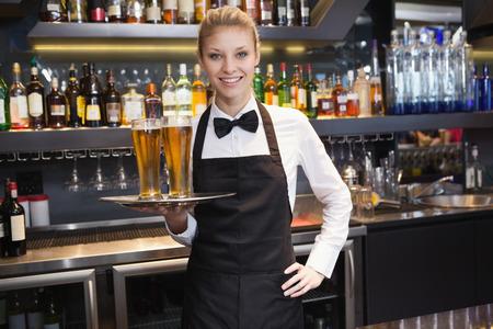 barra de bar: Camarera con la mano en la cadera que sostiene una bandeja de champ�n en un bar