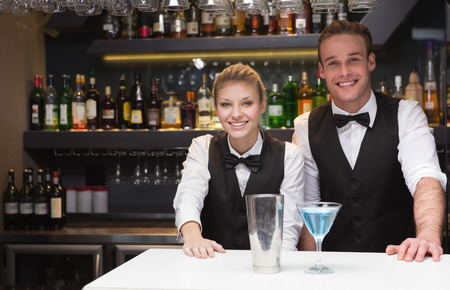 20s waitress: Colleagues smiling at the camera in a bar