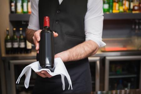 barra: Camarero hermoso que sostiene una botella de vino tinto en un bar