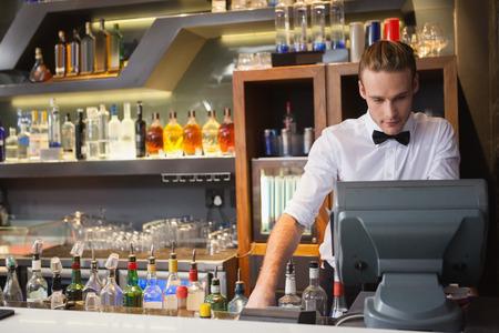 barra: Camarero hermoso que se coloca en la caja registradora en un bar Foto de archivo