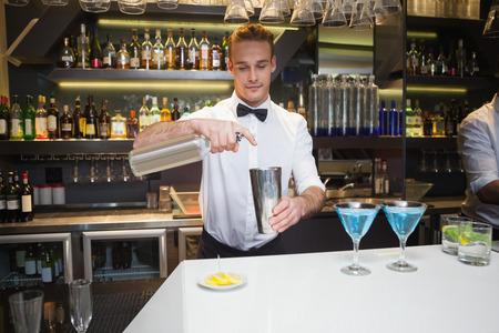 bar: Smiling bartender preparing a drink at bar counter in a bar