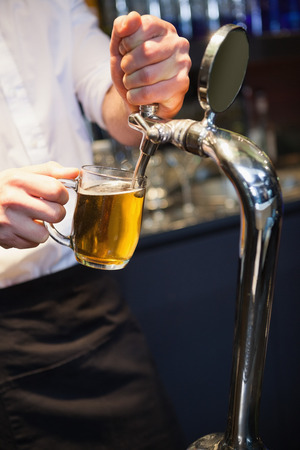 beer pump: Handsome barkeeper pulling a pint of beer in a bar