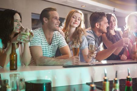 Gelukkige vrienden die samen iets drinken in een bar Stockfoto
