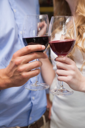Close up of lovely couple enjoying red wine at the nightclub photo
