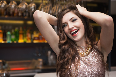 Seductive brunette posing for camera ruffling her hair at the nightclub