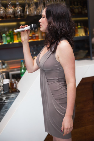 passionately: Pretty girl singing passionately into a microphone at the nightclub