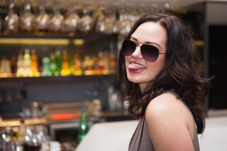 pull out: Pretty woman wearing sunglasses with tongue out at the nightclub