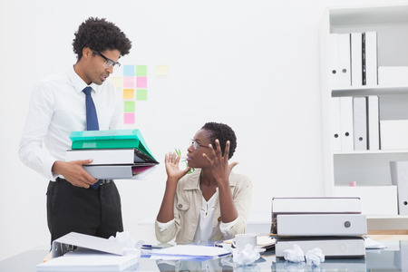 annoy: Man giving pile of files to his irritated colleague in the office