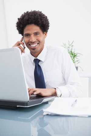 Happy businessman phoning and using laptop in the office photo