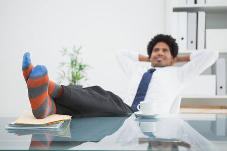 swivel chair: Businessman relaxing in his swivel chair with feet up in his office