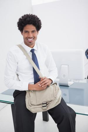 shoulder bag: Smiling businessman with shoulder bag in his office