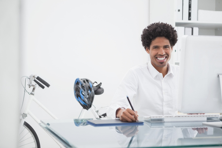 graphics tablet: Happy designer drawing on graphics tablet in his office