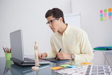 digitizer: Focused designer using digitizer at his desk in his office