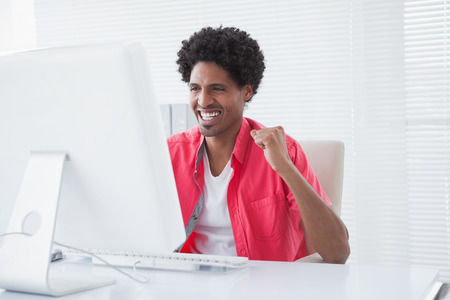 Smiling casual businessman cheering at his desk in his office photo
