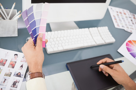 designer chair: Designer working at desk using digitizer and colour sample in his office Stock Photo