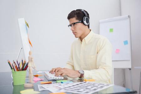 musica electronica: Dise�ador serio escuchar m�sica y trabajando en su oficina Foto de archivo