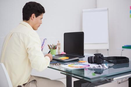 digitizer: Designer using digitizer and colour sample in his office