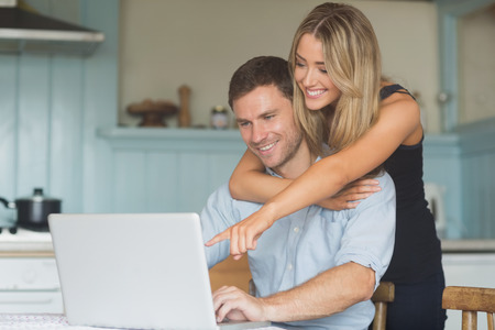 young man smiling: Cute couple using laptop together at home in the kitchen