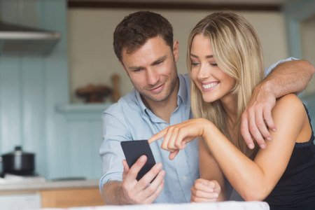 mobile phone adult: Cute couple using smartphone together at home in the kitchen