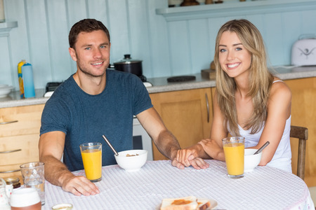 cereals holding hands: Cute couple having breakfast together at home in the kitchen