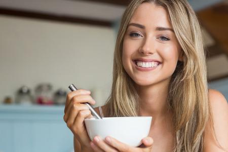 femme blonde: Cute blonde ayant des c�r�ales pour le petit-d�jeuner � la maison dans la cuisine Banque d'images