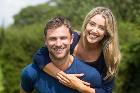couple nature: Cute couple smiling at camera at home in the garden Stock Photo