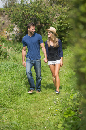 Cute couple walking holding hands at home in the garden photo