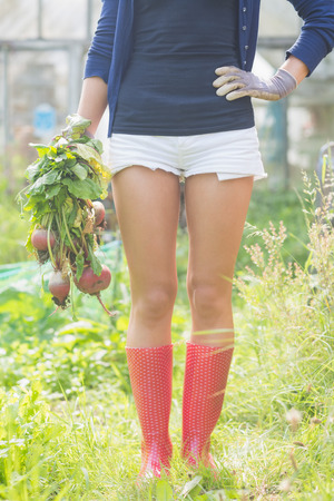home grown: Woman holding home grown vegetables at home in the garden Stock Photo