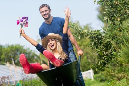 Man pushing his girlfriend in a wheelbarrow at home in the garden Stockfoto