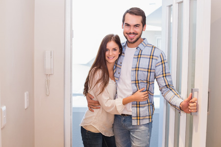 door opening: Cute couple walking through the door in their new home Stock Photo